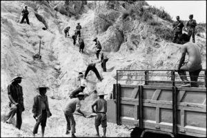 Guards with prisoners digging sand
